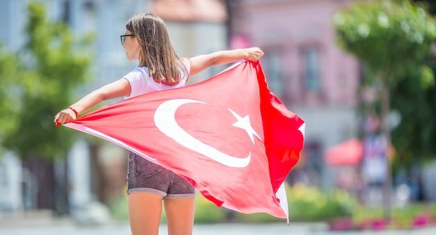 Gelukkig meisje toerist wandelen in de straat met de vlag van turkije.