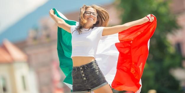 Gelukkig meisje toerist wandelen in de straat met italiaanse vlag.