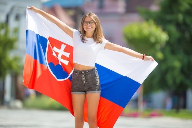 Gelukkig meisje toerist wandelen in de straat met vlag van slowaakse republiek.