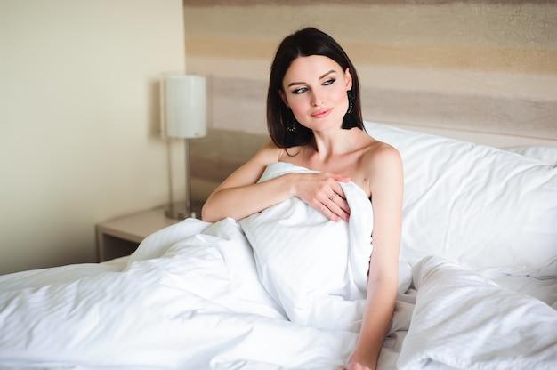 Gelukkig meisje wakker uitrekkende armen op het bed in de ochtend.