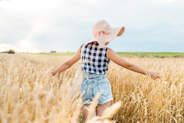 Gelukkig meisje, wandelen in gouden tarwe, met haar rug, buiten levensstijl. vrijheid concept.