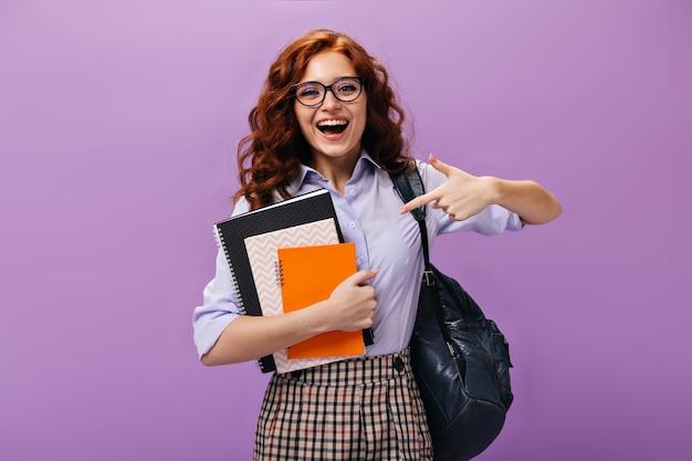 Gelukkig meisje wijzend naar notitieboekjes op paarse muur