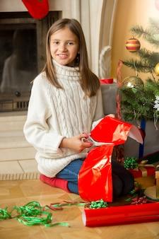Gelukkig meisje zit bij de kerstboom en snijdt rood papier om cadeau in te pakken