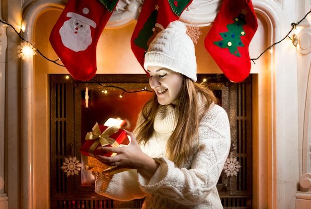 Gelukkig meisje zit bij open haard en kijkt naar cadeau in doos