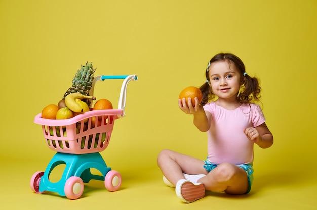 Gelukkig meisje zit in de buurt van een winkelwagentje vol fruit op een geel oppervlak, houdt een sinaasappel vast en toont deze op de camera. geïsoleerd op geel met kopie ruimte