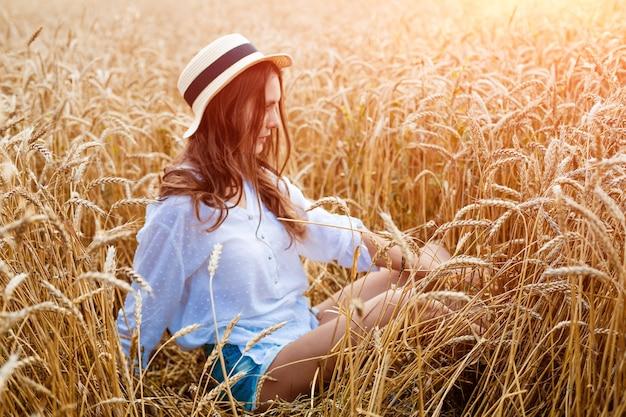Gelukkig meisje zit in tarweveld in strohoed schattige jonge vrouw van blanke etniciteit in vrijetijdskleding...