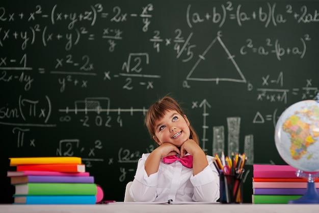 Gelukkig meisje zitten en dromen in de klas