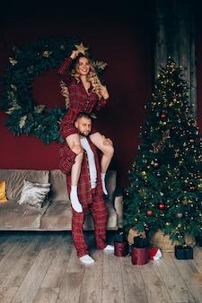 Gelukkig meisje zittend op mamas schouders met gouden ster in de hand. staande op versierde kerstboom.