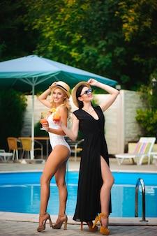 Gelukkig meisjes met dranken op zomerfeest in de buurt van het zwembad.