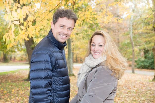 Gelukkig middelbare leeftijd paar verliefd buitenshuis herfstdag knappe man en blonde vrouw