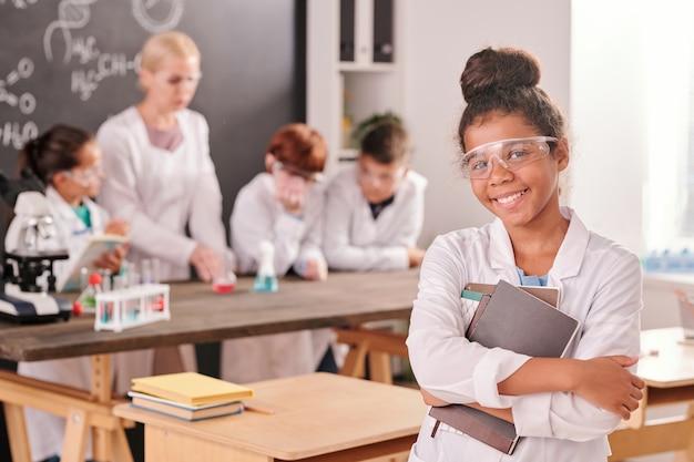 Gelukkig middelbare schoolmeisje van gemengd ras in witte jas die naar je kijkt met een brede glimlach tegen klasgenoten en leraar tijdens laboratoriumwerk