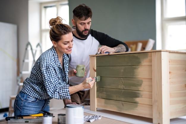 Gelukkig midden volwassenen paar schilderen meubels binnenshuis, verhuizing en doe-het-concept.