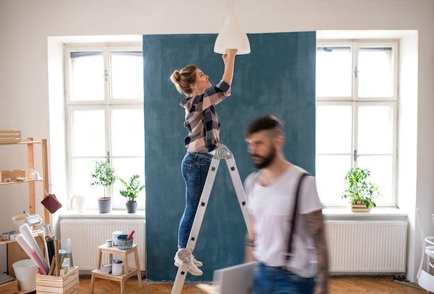 Gelukkig midden volwassenen paar veranderende gloeilamp binnenshuis thuis, verhuizing en diy concept.
