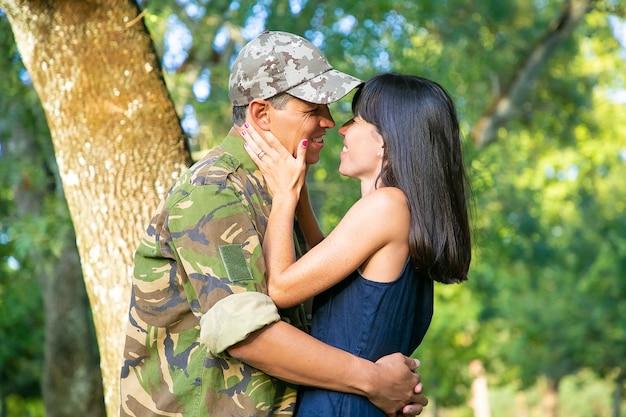 Gelukkig militaire man en zijn vrouw knuffelen en kussen in stadspark. zijaanzicht, gemiddeld schot. terug naar huis of relatieconcept