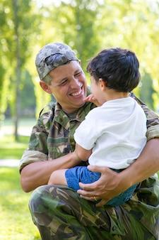 Gelukkig militaire vader zoontje in armen houden, jongen buiten knuffelen na terugkeer van zendingsreis. familiereünie of het concept van thuiskomst