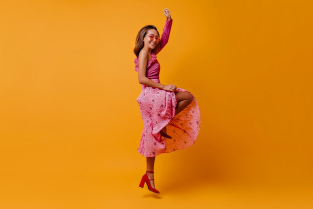 Gelukkig, minzaam vrouwelijk model in geplooide lange rok die stuitert en sierlijke slanke benen in ongebruikelijke schoenen laat zien. brunette met bril heeft plezier