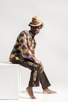 Gelukkig mode afrikaanse man in traditionele kleding zitten op kubus