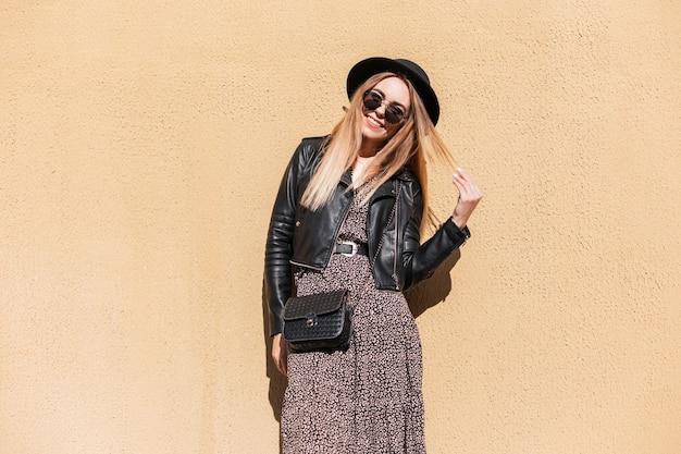 Gelukkig mode vrouw met herfst trendy outfit in stijlvolle leren jas en jurk met zwarte kleine tas