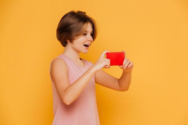 Gelukkig modern meisje die smartphone voor geïsoleerde opnamevideo gebruiken