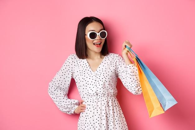 Gelukkig moderne aziatische vrouw gaan winkelen in winkelcentra, tassen met kleding houden en glimlachen, zonnebril dragen, staande over roze
