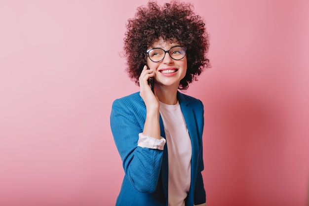 Gelukkig moderne vrouw draagt een bril en een blauwe jas praten aan de telefoon met een charmante glimlach op roze