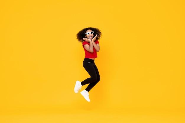Gelukkig modieus afrikaans amerikaans meisje dat in mid-air met handen op kin springt die op gele muur wordt geïsoleerd