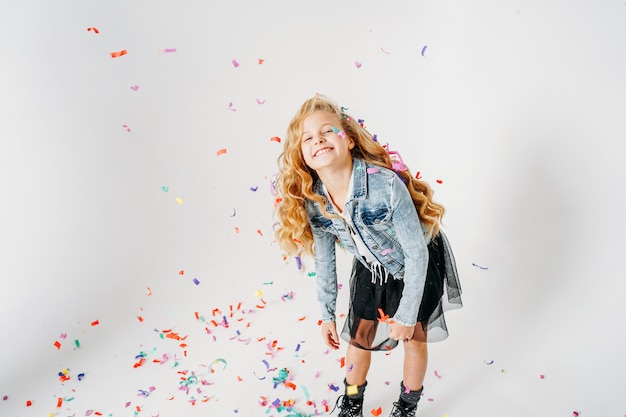 Gelukkig modieus gekleed krullend haar-tween-meisje in een spijkerjasje en zwarte tutu-rok en ruwe laarzen op wit met kleurrijke confetti