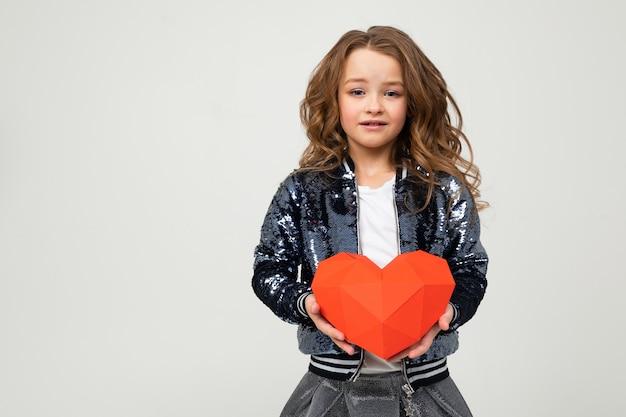 Gelukkig modieus meisje dat een rood document hart op een witte muur met lege ruimte houdt
