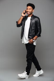 Gelukkig modieuze afro americam man met hand in zijn zak praten op mobiele telefoon, op zoek