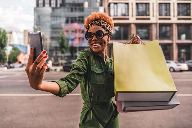 Gelukkig modieuze jonge vrouw selfie maken op smartphone en boodschappentassen in de hand houden in de stad