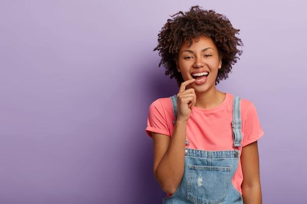 Gelukkig modieuze vrouw glimlacht zorgeloos, draagt t-shirt en denim overall, houdt wijsvinger op de lippen, geïsoleerd op paarse achtergrond