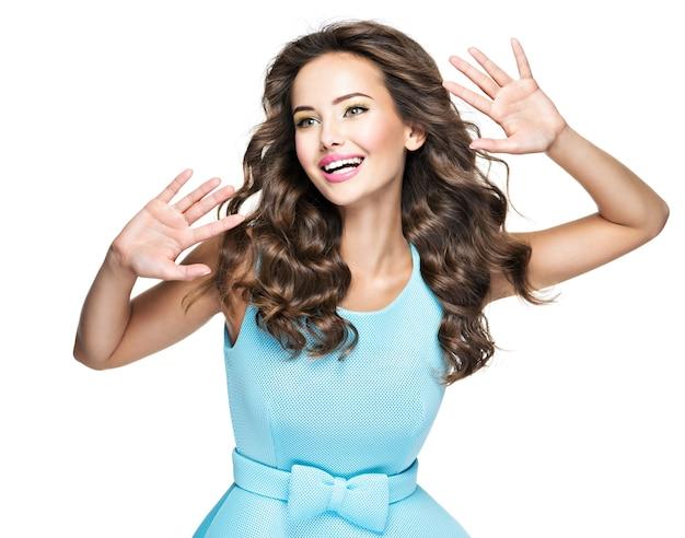 Gelukkig modieuze vrouw met expressieve emoties. mooie mannequin in blauwe jurk op witte achtergrond