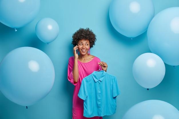 Gelukkig modieuze vrouw praat met vriend aan de telefoon, houdt blauw stijlvol shirt op hanger, kleedt zich op kippenfeestje, vertelt over de laatste aankoop in de kledingwinkel. mensen, stijl, kleding en feest