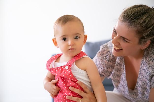 Gelukkig moeder bedrijf babymeisje, glimlachend en kijken naar haar. ernstige schattige peuter in rode tuinbroekbroek. mooie moeder praten met kind. familie tijd en moederschap concept
