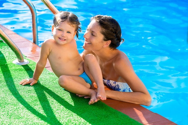 Gelukkig moeder en baby dochter zwembad