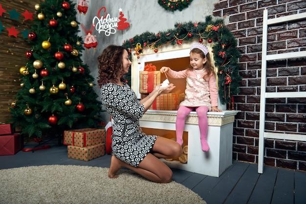 Gelukkig moeder en dochter bij de open haard voor wintervakantie. kerstavond en oudejaarsavond.