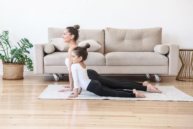 Gelukkig moeder en dochter doen yoga samen thuis