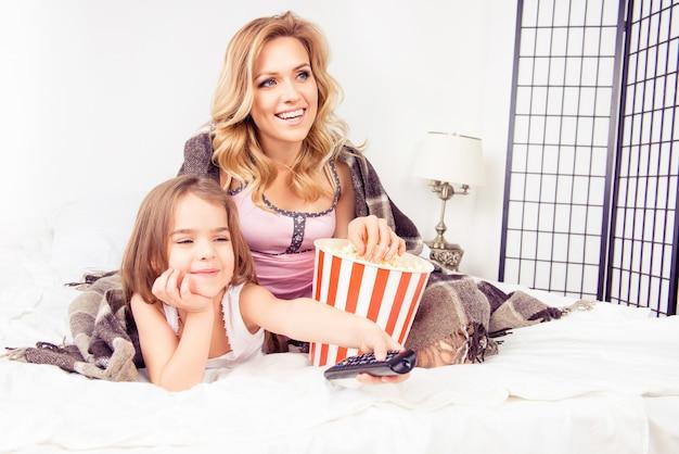 Gelukkig moeder en dochter kijken naar tekenfilms en popcorn eten