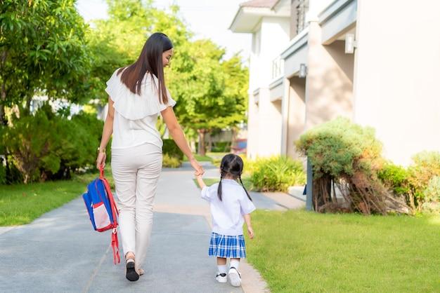 Gelukkig moeder en dochter kleuterschool student lopen naar school