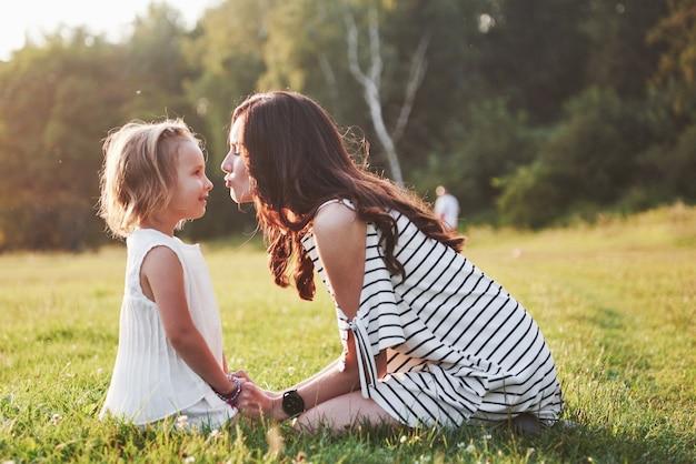 Gelukkig moeder en dochter knuffelen in een park in de zon op een lichte zomer achtergrond van kruiden.