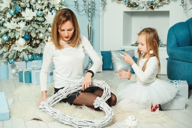 Gelukkig moeder en dochter maken van decoraties voor kerstfeest.