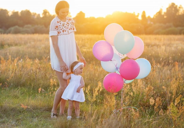 Gelukkig moeder en dochter met ballonnen buiten