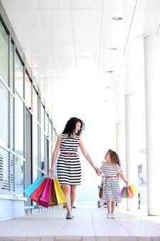 Gelukkig moeder en dochter met winkeltassen, buitenshuis