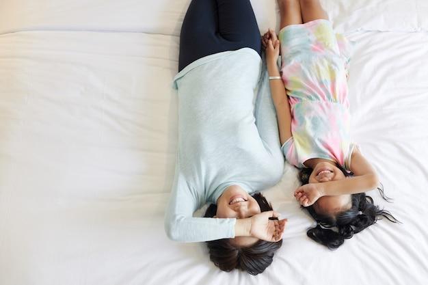 Gelukkig moeder en dochter ontspannen op bed na samen spelen, bekijken van bovenaf