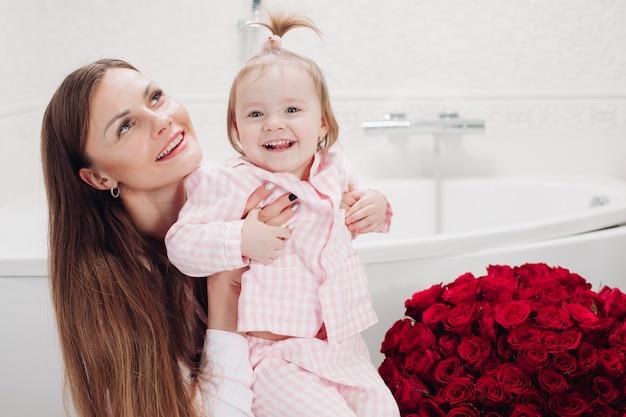 Gelukkig moeder en dochter zitten in de badkamer in de ochtend