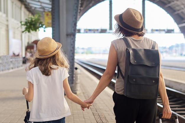 Gelukkig moeder en dochterkind dat samen op station loopt met bagagekoffer, achteraanzicht. reizen, toerisme, transport, familieconcept