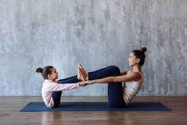 Gelukkig moeder en dochterkind die samen sportenyoga op de mat doen