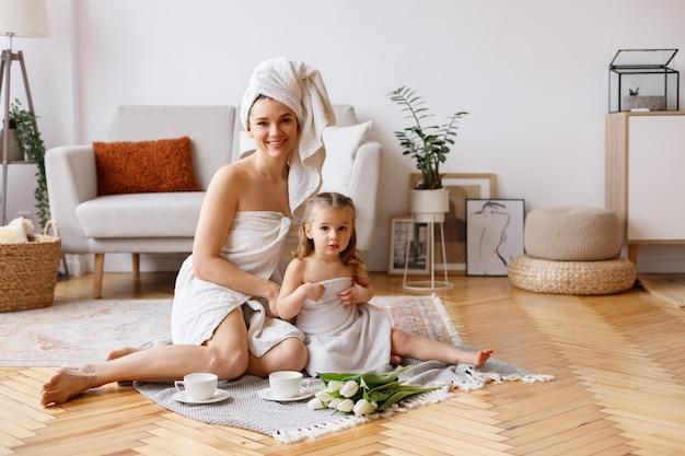 Gelukkig moeder en dochters in handdoeken thuis