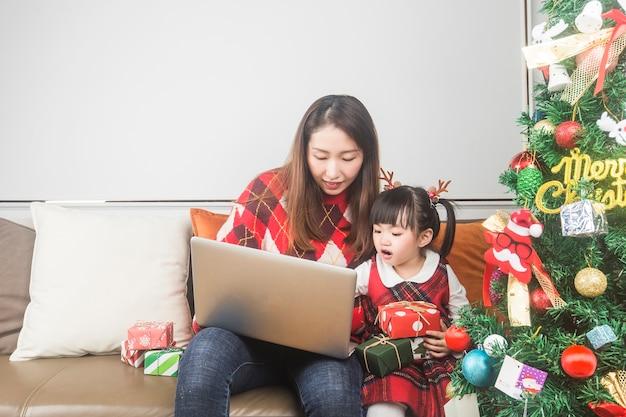 Gelukkig moeder en dochtertje kerstboom en geschenken thuis versieren