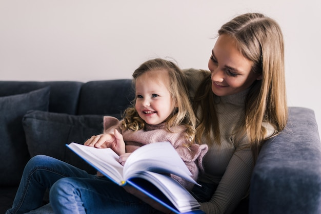 Gelukkig moeder en dochtertje leesboek, zittend op een comfortabele bank in de woonkamer